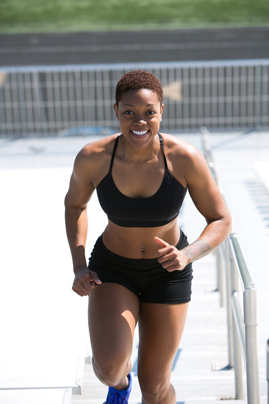 woman wearing black sports bra and jogger shorts smiling
