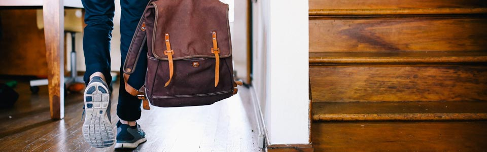 Designer walking down a hallway carrying a back pack to go and see for themselves.