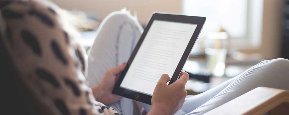 Woman reading an ebook on a tablet.