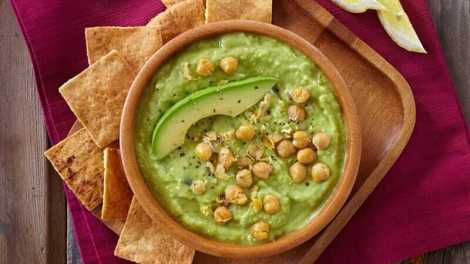 Bowl of avocado-hummus dip with chick peas on top