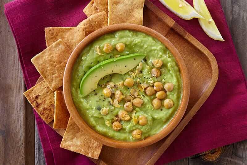 Bowl of avocado-hummus dip with chick peas on top
