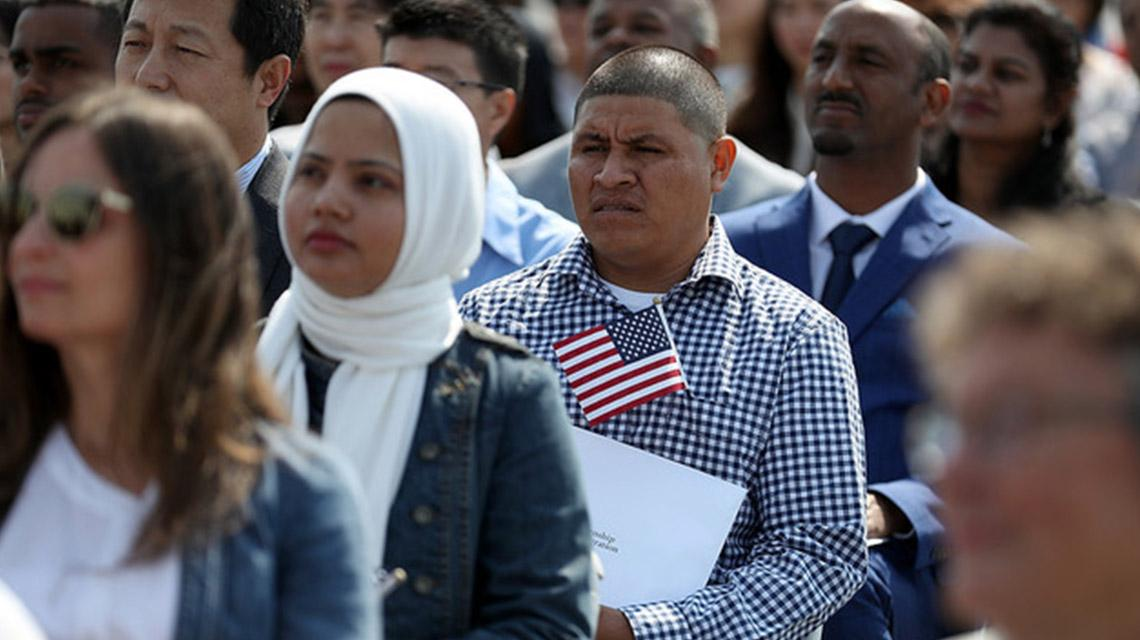 Immigrant standing while holding the U.S flag