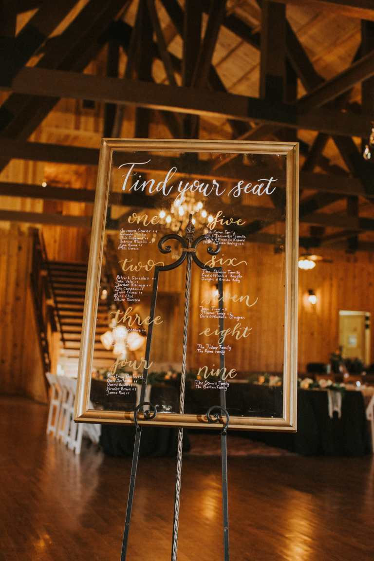 Clear Acrylic Glass Wedding Seating Chart with White and Gold Calligraphy at The Milestone Boerne by CalliRosa Calligrapher in San Antonio Texas