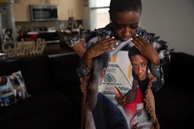 """Maraston, quien sostiene una manta con fotos de su hijo, fundó la organización sin fines de lucro Peace Beyond the Pain para apoyar a otras familias cuyos seres queridos fueron víctimas de homicidio. """"La gente no comprende los efectos secundarios"""", dijo. """"Todavía tengo que ser esta mamá y mantenerme unida para los otros niños también, porque si me ven desmoronándome, ¿qué van a hacer?"""" Foto de Shelby Tauber para CalMatters"""
