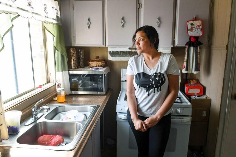 Carolina Navarro, de 34 años, se encuentra en la cocina de su casa móvil en Cantua Creek el 2 de marzo de 2021. Navarro está divorciada, tiene dos hijos y no tiene trabajo desde noviembre. Foto de Craig Kohruss, The Fresno Bee