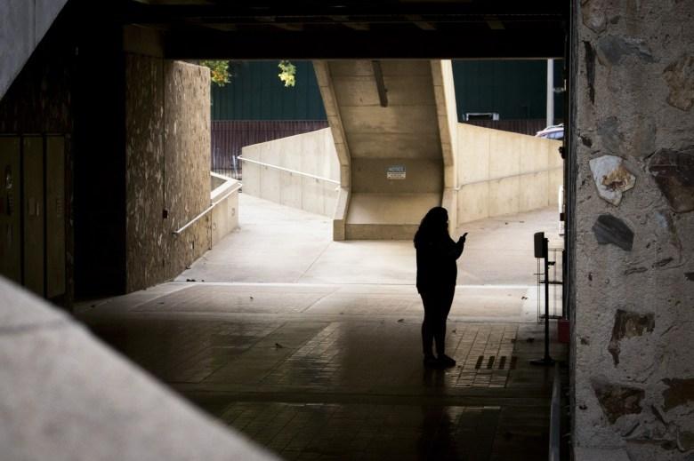 Un estudiante revisa su teléfono mientras espera el ascensor debajo del Eureka Hall en la Universidad Estatal de Sacramento el 9 de noviembre de 2020. Con pocos estudiantes en el campus, la calle, que normalmente es muy transitada, permaneció en silencio durante gran parte del día. Foto de Rahul Lal
