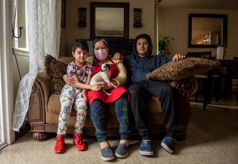 Dylan Domingo, de 8 años, se sienta junto a su madre Blanca Esthela Trejo, en el centro, y su hermano mayor Illian Domingo, de 18, dentro de su casa en Salinas el 22 de abril de 2021. Foto de David Rodríguez, The Salinas Californian