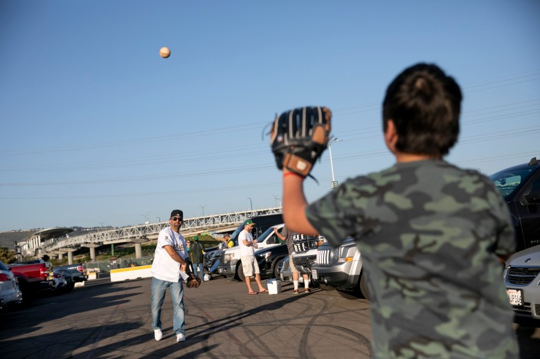 """Perry Farahani lanza una pelota de béisbol con su hijo Jacob, de 12 años, en el estacionamiento del Coliseum. """"Es diferente de lo normal, pero lo aceptaré"""", dijo sobre no poder abrir la puerta trasera. Foto de Anne Wernikoff, CalMatters"""