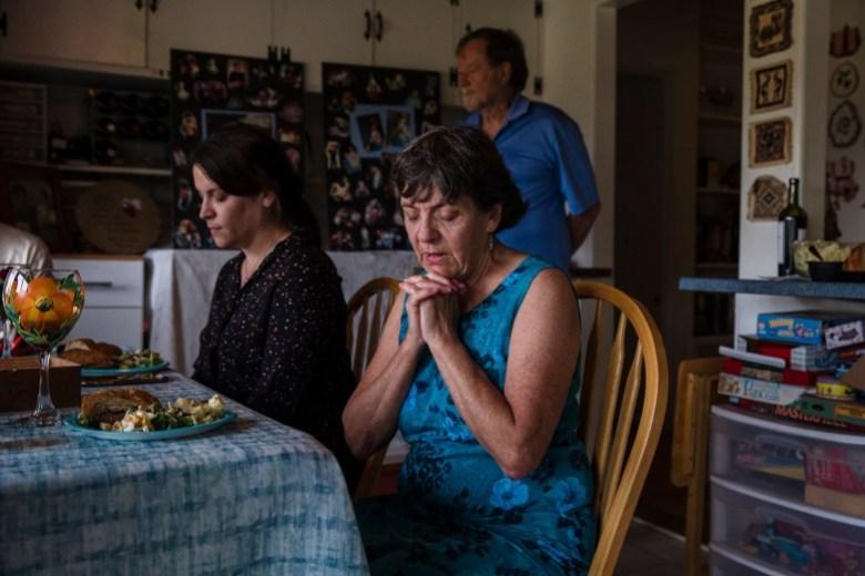 """Kathleen Bils dice una oración en su casa antes de almorzar con familiares y amigos que asistieron para recordar a su hijo Nicholas """"Nicky"""", quien fue asesinado a tiros por un alguacil del condado de San Diego después de escapar de un camión de guardaparques en esposas fuera de la cárcel del condado. Foto de Ariana Drehsler para CalMatters"""