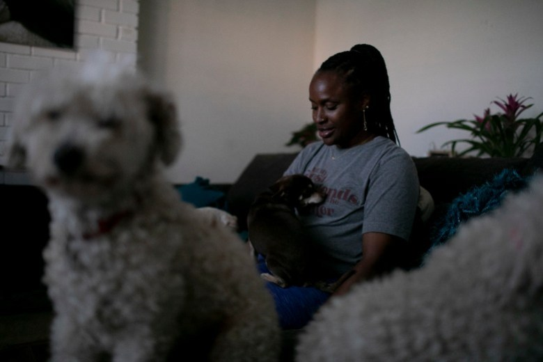 Merika Reagan juega con sus perros, Jordan, una mezcla de chihuahua y sus dos caniches, Goldie y Conseulo, en la sala de su casa de Oakland. Foto de Anne Wernikoff, CalMatters