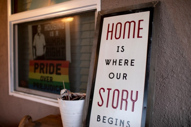 Letreros en el porche de la casa de Merika Reagan en Oakland que muestran el apoyo al derecho a la vivienda y el orgullo gay. Foto de Anne Wernikoff, CalMatters
