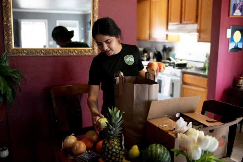 Claudeth desempaca víveres y comidas gratis entregados por el Distrito Escolar Unificado de Oakland. Foto de Anne Wernikoff, CalMatters