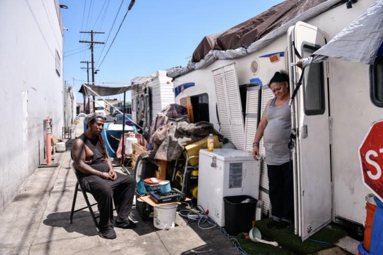Rafael Suárez y April Lei se quedan afuera de su casa rodante para tratar de mantenerse frescos durante un día caluroso en Los Ángeles, el 9 de julio de 2021. La pareja ha vivido en esta cuadra durante un año y medio, según la pareja. Pablo Unzueta para CalMatters