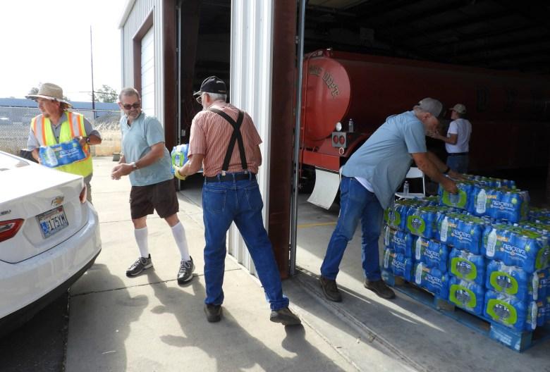 Los voluntarios distribuyen suministros de agua embotellada a personas con pozos secos en el Departamento de Bomberos de Orland en el condado de Glenn el 28 de julio de 2021. Algunos voluntarios estaban lidiando con cortes de pozos, ellos mismos. Foto de Rachel Becker, CalMatters