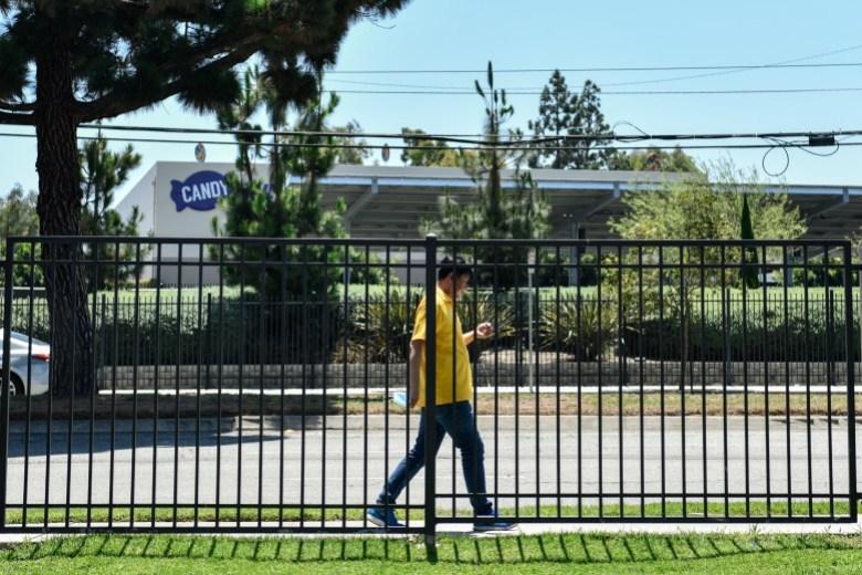 Un hombre camina a lo largo de una cerca ubicada cerca del hotel Residence Inn by Marriott en Long Beach, el 30 de julio de 2021. El hotel es donde Rasheena McCord y sus hijos viven temporalmente después de que fue desalojada. Foto de Pablo Unzueta para CalMatters
