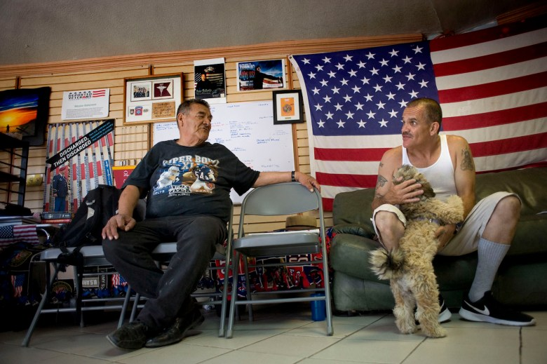 Deported U.S. military veterans Andrew De Leon, left, and Alejandro Gomez Cortez, chat at the Deported Veteran's Support House. Photo by David Maung for CALmatters