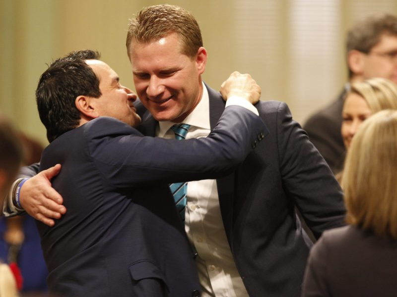 Democratic Assembly Speaker Anthony Rendon embraces former Assembly GOP leader Chad Mayes in December of 2016. Photo by Steve Yeater for CALmatters