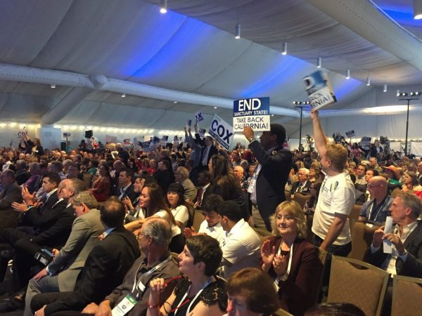 A crowd of seated and standing California Republican delegates cheer and wave signs in a tented pavilion
