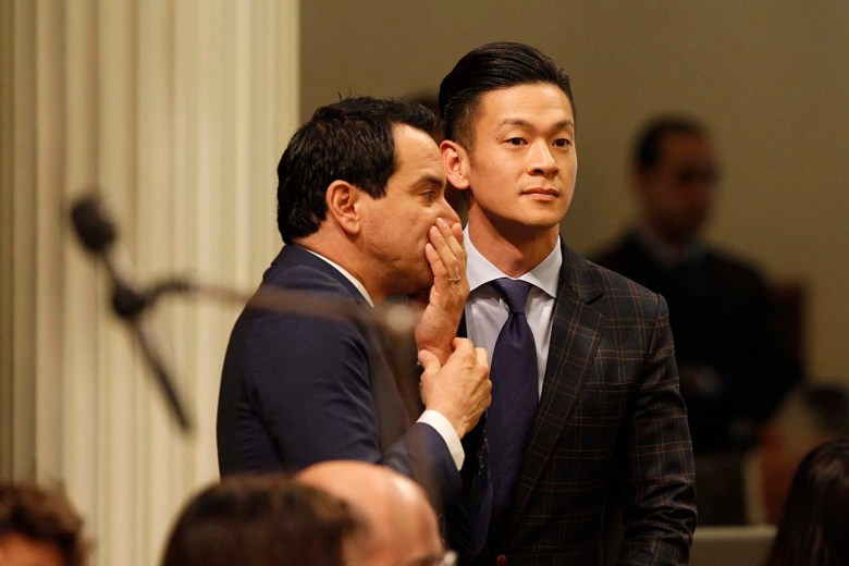 Evan Low listens as another man speaks to him on the Assembly floor.