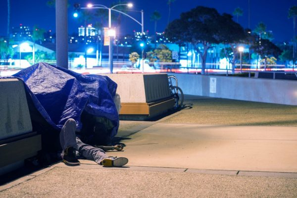 Homeless person sleeping in urban scape—emblematic of where poverty rates are worsening. Photo via Adobe Stock