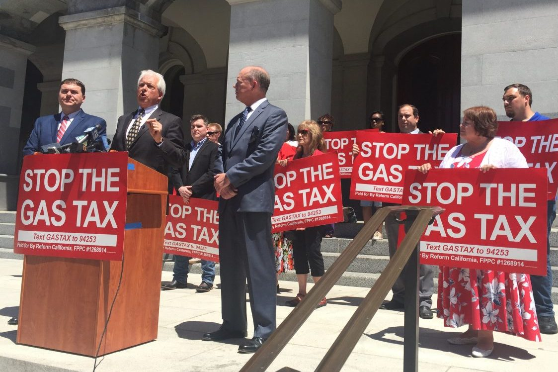 "Leaders of the Proposition 6 ballot initiative speak to the press outside the capitol building. In the front are Carl DeMaio, chairman of Reform California; John Cox, Republican candidate for governor; Jon Coupal, President of the Howard Jarvis Taxpayers Association. Behind them are supporters with ""Stop the Gas Tax"" signs."
