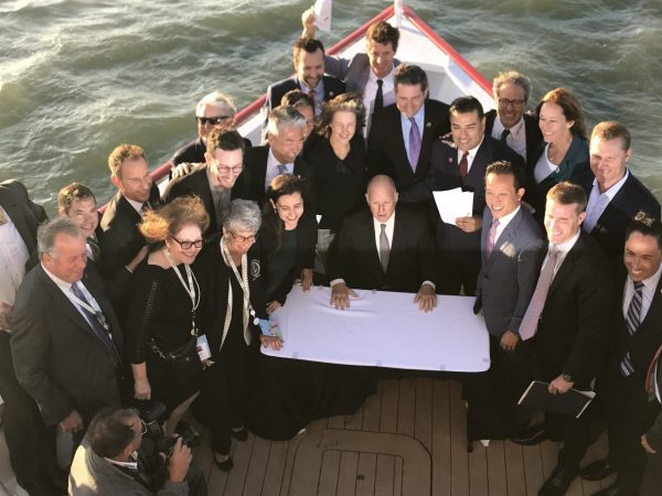 Gov. Jerry Brown signs clean energy bills on the deck of a hybrid ferry in San Francisco, Sept. 13, 2018.