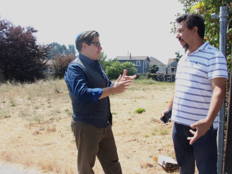 Councilmember Rebecca Kaplan speaks with property owner Francisco Acosta in front of a vacant lot in West Oakland on Aug. 20, 2018. Kaplan authored a proposed tax on vacant properties to help ease homelessness in the city. Photo by Farida Jhabvala Romero/KQED