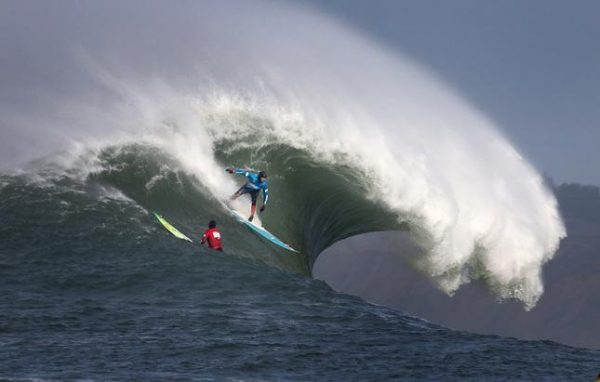 Peter Mel of Santa Cruz takes off on a wave in the 2014 Mavericks Big Wave surfing contest—a competition that's become a flash point for gender pay equity in California. Photo by Patrick Tehan/Bay Area News Group