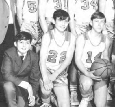 A yearbook photo of the H. L. Richards High School freshman high school team. John Cox, as the manager, kneels to the left of the players wearing a suit jacket and tie.