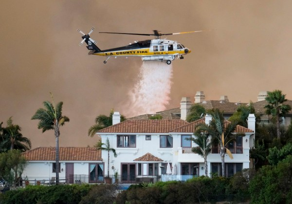 A helicopter drops water on a brush fire behind a home during the Woolsey Fire in Malibu. AP Photo by Ringo H.W. Chiu