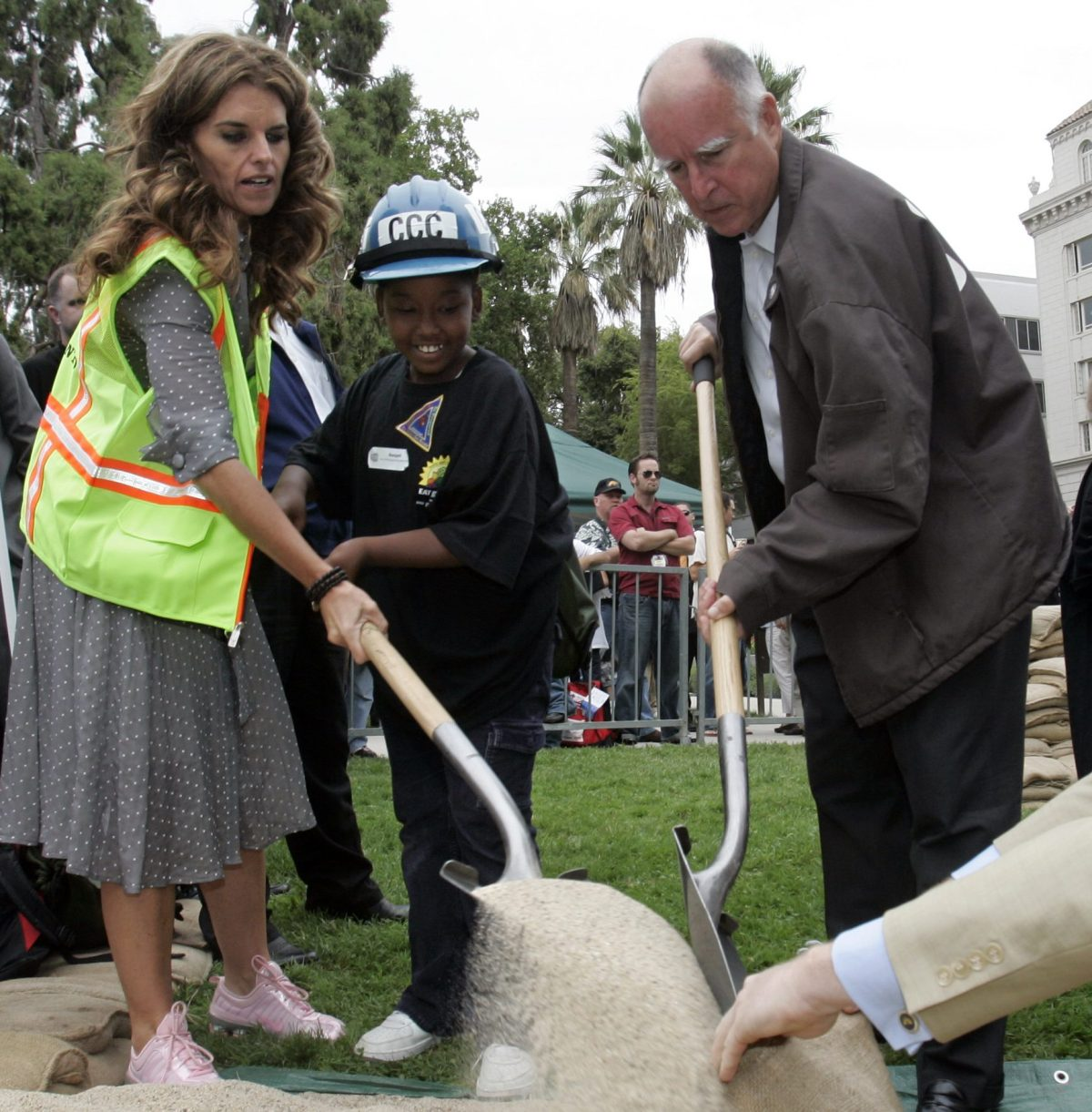 California first lady Maria Shriver, left, helps Auviyonti Jefferson, 9, center, and Oakland Mayor Jerry Brown, fill a sandbag during a visit to a California Conservation Corps exhibit in 2006. Photo by Rich Pedroncelli, Associated Press