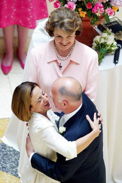 United States Senator Sen. Dianne Feinstein looks on as Oakland Mayor Jerry Brown and Anne Gust embrace after being married at the Rotunda Building in Oakland, CA on June 18th, 2005. Photo by Sean Connelley, East Bay Times