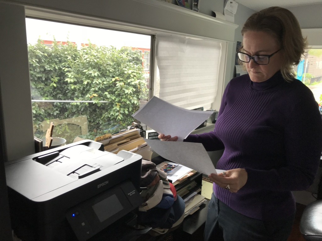 Heather Altman looks through old health insurance bills in her Long Beach home office. Photo by David Wagner, KPCC