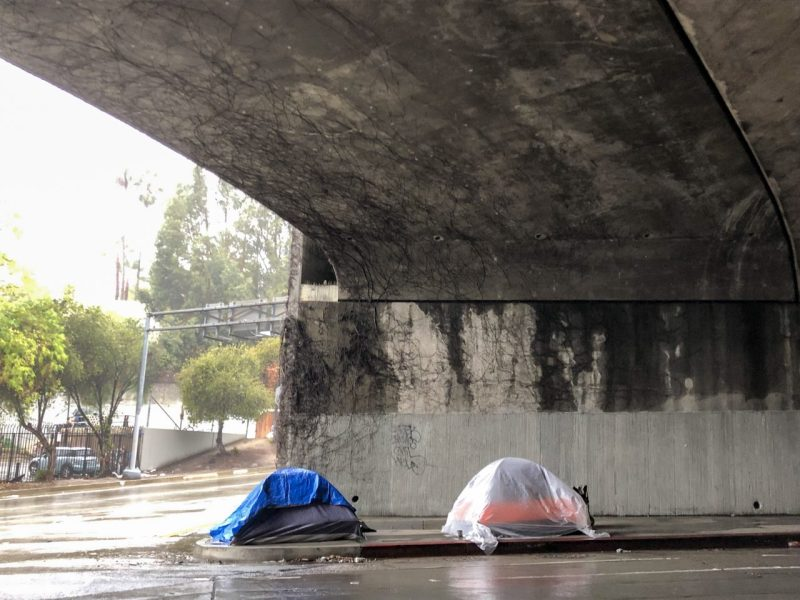 Tents erected beneath the Hollywood Freeway during a rainstorm in Los Angeles. Photo by Matt Tinoco, KPCC