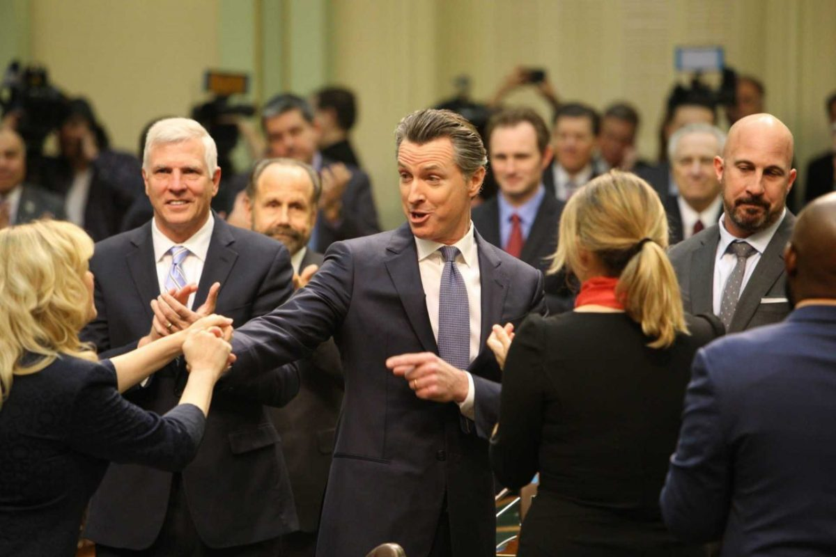 Gov. Gavin Newsom surrounded by legislators at the 2019 State of the State address in the Capitol. Photo by Andrew Nixon, Capital Public Radio