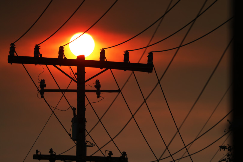 Power lines are silhouetted by the sun seen through a smoky sky in Oakland, Calif., on Saturday, June 30, 2018. According to the National Weather Service, smoke comes from fires in Yolo County and beyond. (Ray Chavez/Bay Area News Group)