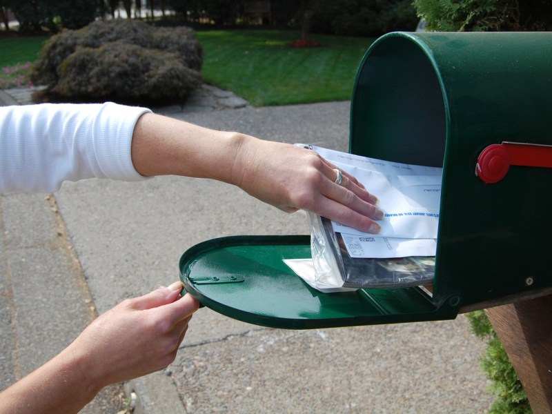 Woman's arm gathering a bundle of mail from a mailbox. A Trump administration proposal would have Covered California participants receiving an extra bill of $1 every month for abortion coverage.
