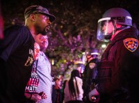 Photo of a Black Lives Matter protestor staring at a California Highway Patrol officer at a Sacramento protest following the police shooting of Stephon Clark. Photo by Max Whittaker.