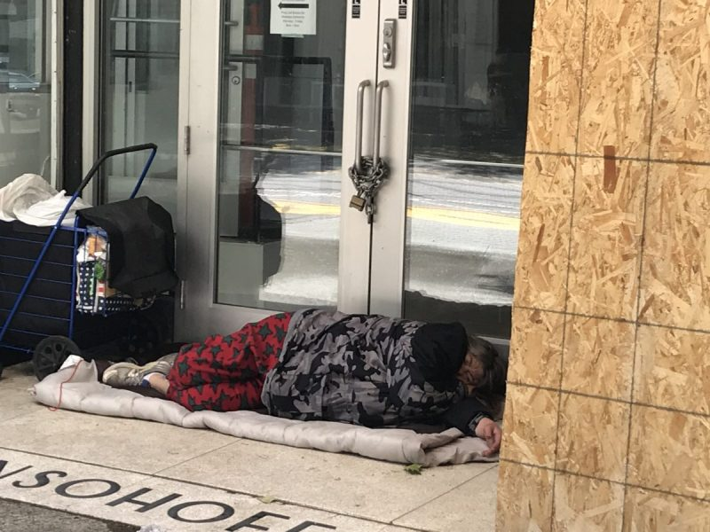 A woman sleeps in a doorway in downtown Sacramento, near the state Capitol where lawmakers are negotiating over how to spend homeless funds. Photo by Dan Morain for CALmatters