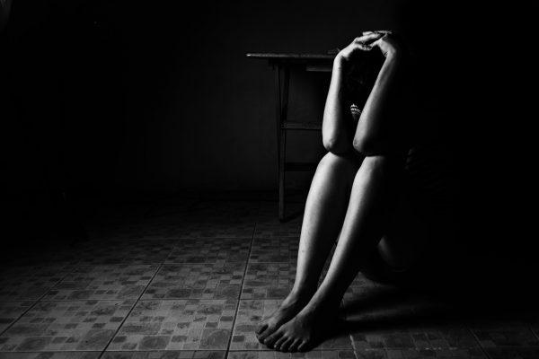 a woman sitting on ground with arm around lower head, sexual violence , sexual abuse, human trafficking concept