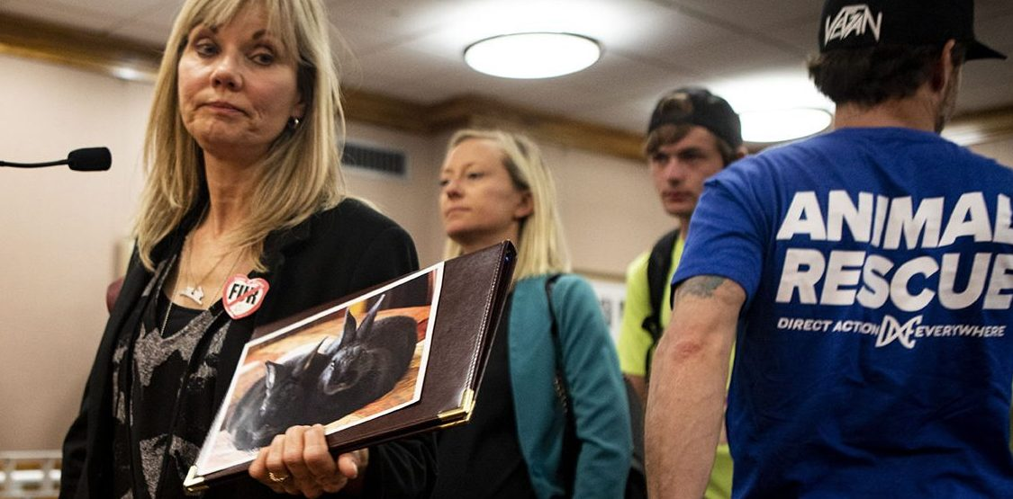 Animal rights advocate Deborah Classen holds a poster featuring rabbits to support a bill that would ban fur from wild animals., at a Capitol hearing July 9, 2019.