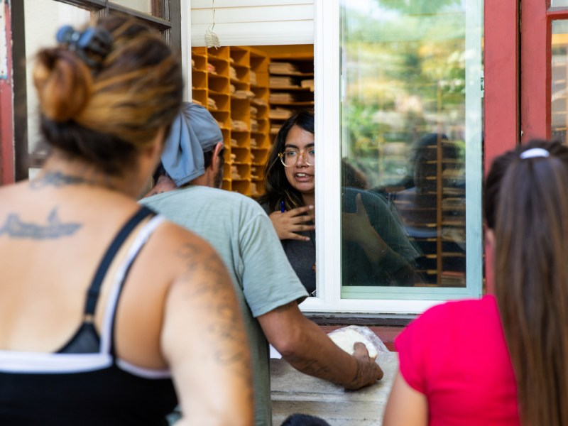 Yaritza Cordova, center, a community worker with Catholic Charities of Santa Clara County, signs up Maurice Castro for mail service at the window outside of Catholic Charities John XIII Multi Service Center in San Jose. People who are homeless use the service to receive mail and enroll their children in school. Photo by Randy Vazquez, Bay Area News Group