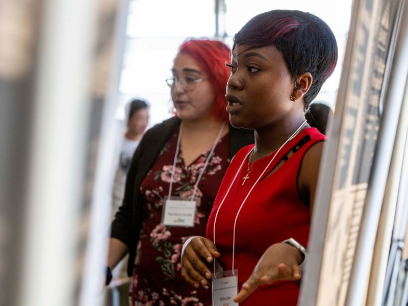 UC Merced undergraduate Kaline Leke, at right, makes a presentation on her research project. Photo by Anne Wernikoff for CalMatters