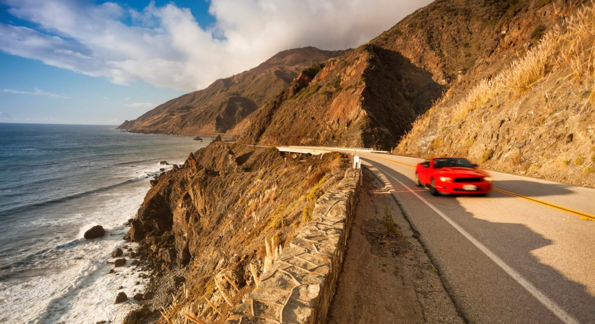 A convertible is driven along the coastline in Big Sur, California. Photo by Pgiam/istockphotos.com