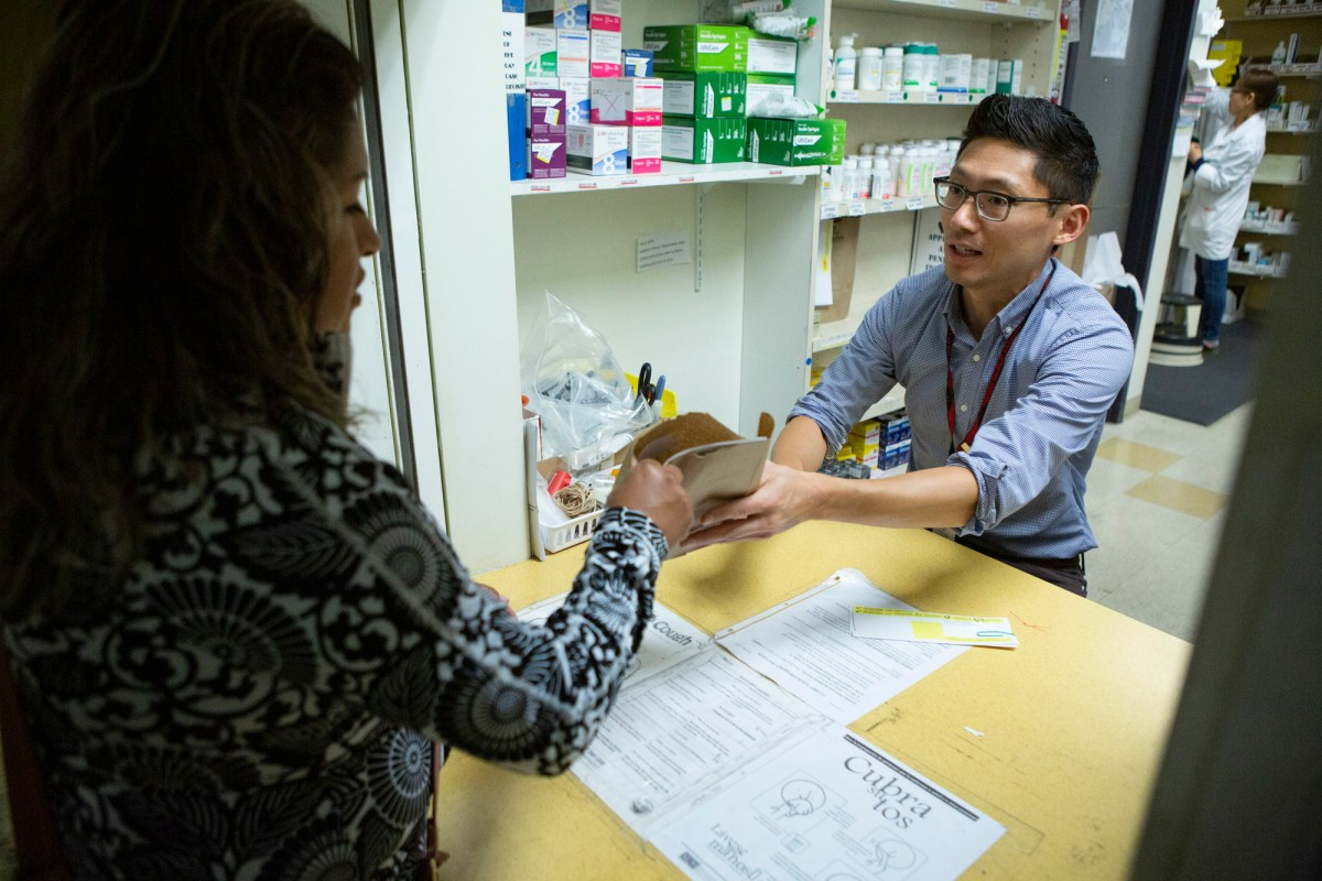 Pharmacist James Lee hands a patient her prescription at La Clinica on September 26, 2019. Photo by Anne Wernikoff for CalMatters