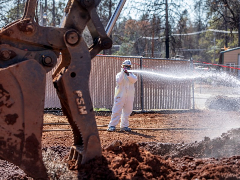 A worker douses potentially contaminated soil n Paradise, California, 11 months after the Camp Fire. Photo by Anne Wernikoff, CalMatters