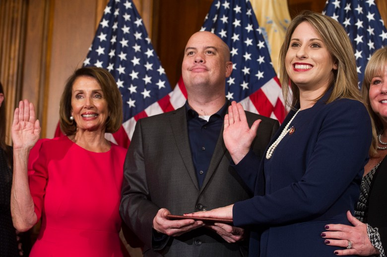 House Speaker Nancy Pelosi swears in Rep. Katie Hill, with Hill's now-estranged husband, Kenny Heslep, during the opening session of the 116th Congress in January. AP Photo/Cliff Owen