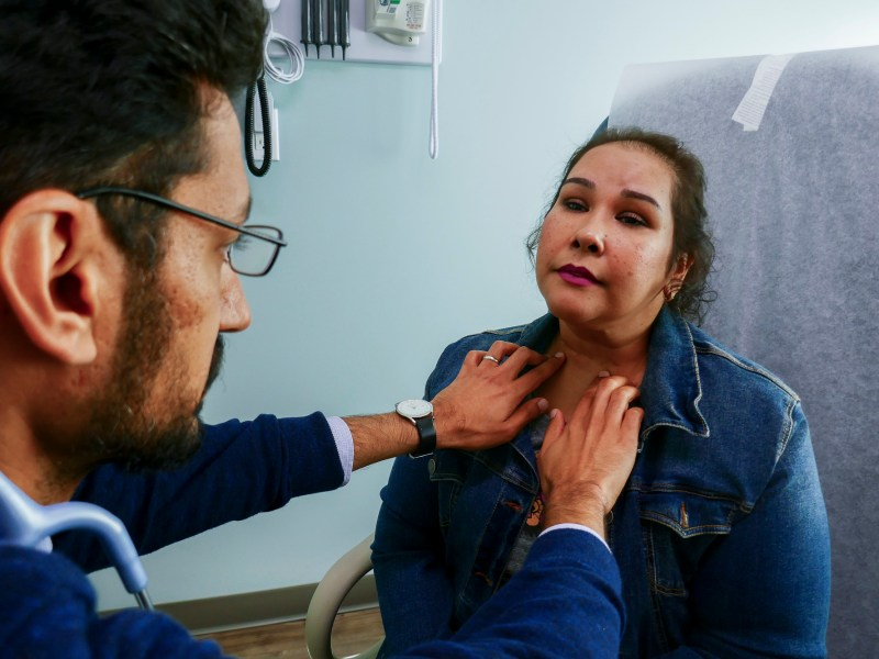 Dr. Moazzum Bajwa examines Cesilia Jimenez's neck during a recent appointment at the Moreno Valley Community Health Center. Jimenez had a cancerous tumor removed from her neck several years ago after Bajwa discovered it when he was a resident doctor in training. He's still her doctor and is now an attending physician and is curriculum director of the residency program. Photo by Elizabeth Aguilera for CalMatters