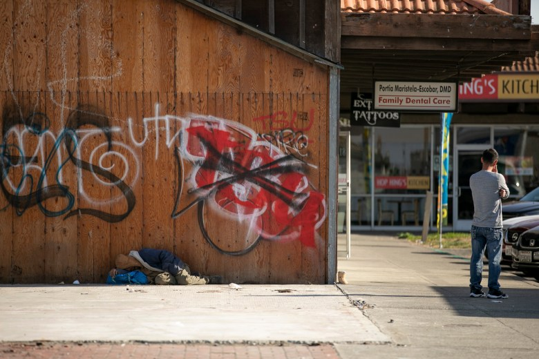 Mark Rippee sleeps along a wall at a strip mall in Vallejo on November 22, 2019. As the nights become colder Rippee prefers to sleep during the day. Photo by Anne Wernikoff for CalMatters