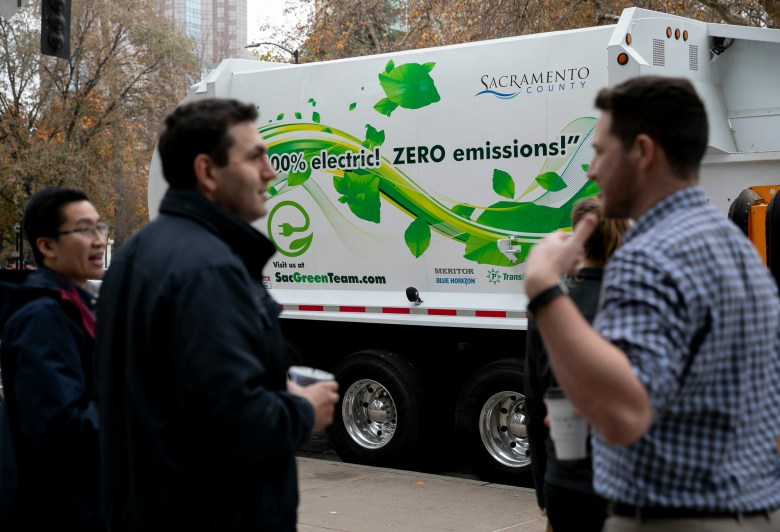 Electric trucks are displayed outside of the California EPA. Photo by Anne Wernikoff for CalMatters